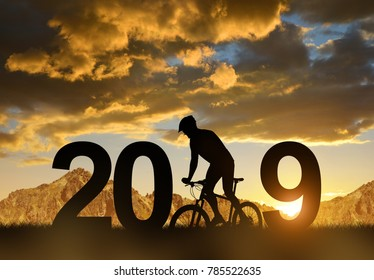 Silhouette of a cyclist on bike in the sunset. Concept of New Year 2019.