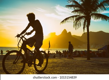 Silhouette of a cyclist passing in front of dramatic sunset scene on Ipanema Beach in Rio de Janeiro, Brazil