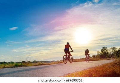 Silhouette of cyclist riding Bike on road at sunset.