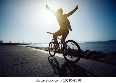 silhouette cyclist riding bike in the sunrise coast road
