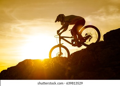 Silhouette of Cyclist Riding Down the Mountain Bike on the Rocky Hill at Sunset. Extreme Sport Concept.