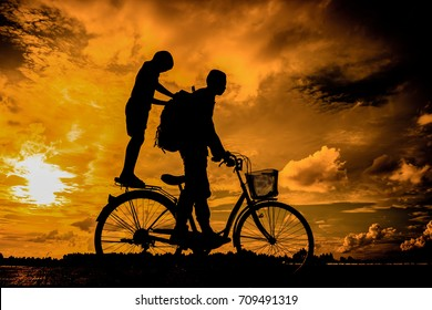 silhouette of the cyclist riding a road bike at sunset, boy Life style outdoor