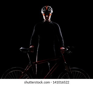 Silhouette of a cyclist standing straight and holding the bicycle in front of him on black background