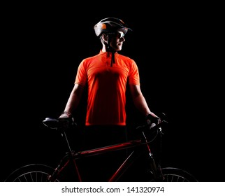 Silhouette of a cyclist standing straight and holding the bicycle in front of him on black background looking to the copy space area