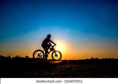Silhouette of cyclist in sunset background.