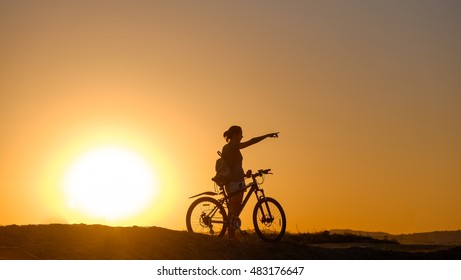 Silhouette of a cyclist who shows his hand direction at sunset