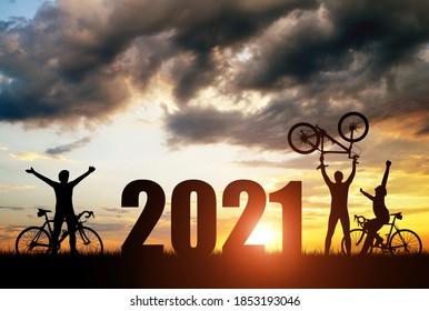 Silhouette der Radfahrer mit Fahrrädern bei Sonnenuntergang. Vorwärts zum Neujahr 2021. Urlaubskonzept.