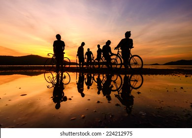 Silhouette cyclists with reflection