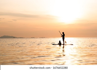 Silhouette of dad and son playing the stand-up paddle board on the sea with beautiful summer sunset colors. Happy family concept.