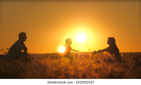 Silhouette of a daddy circling a small child in flight at sunset. Father's day. A daughter with a parent is playing a game against the background of the sky. Kid soar in the air at dawn. Teamwork