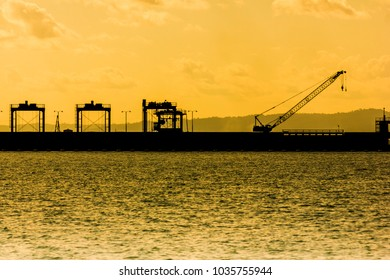 Silhouette of the dam at colorful sunset and over color. With parking Heavy machinery