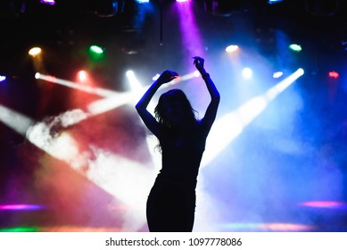 Silhouette of dancing girl against disco lights