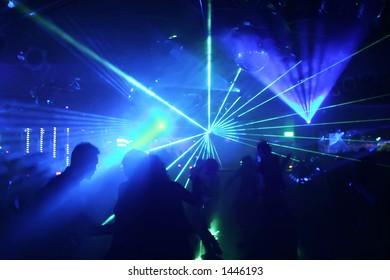 silhouette of dancing people between laser-beams