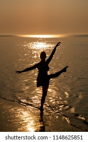 Silhouette of a dancing woman at sunset on the beach of Ouddorp, The Netherlands