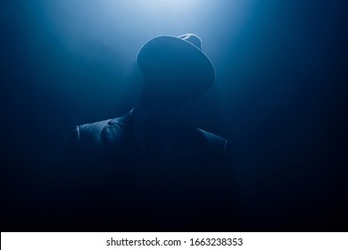 Silhouette of dangerous gangster in suit and felt hat on dark background