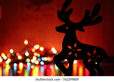 A silhouette of deer (toy) near colorful lights. Creating Christmas mood.