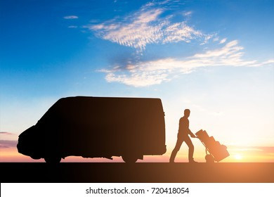 Silhouette Of Delivery Courier With Cardboard Boxes On Trolley Near The Van At Sunset