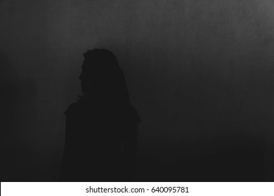 silhouette of depress woman standing in the dark, white tone