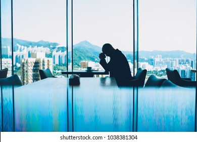 Silhouette of depressed male proud CEO tired from hard work and unsuccessful business project sitting at table with cup of coffee in modern interior. Alone entrepreneur in crisis hold head in despair