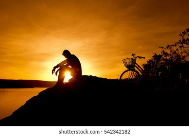 Silhouette Depressed young man sitting on a rock. With his bike on the waterfront on sunset