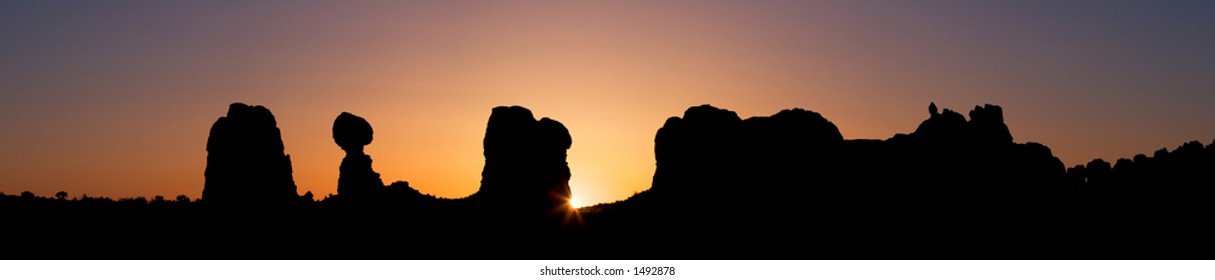 Silhouette of desert rocks, including balanced rock (second from right) - sunrise in Arches National Park, Utah, USA.