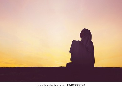 Silhouette of devout woman praying to the Allah while sitting on the hill at sunset time