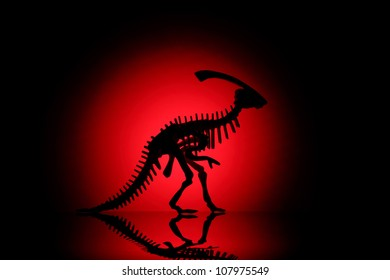 Silhouette of dinosaur on black with reflection.