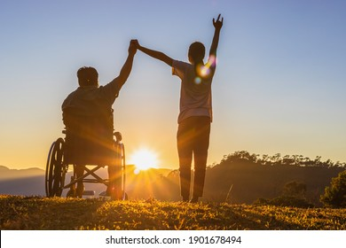 Silhouette Disabled handicapped young man in wheelchair raised hands with his care helper in sunset.