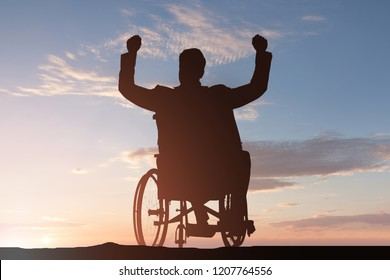 Silhouette Of A Disabled Man On Wheelchair With Arm Raised At Sunset