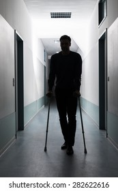 Silhouette Of Disabled Man Walking With Crutches In Hospital