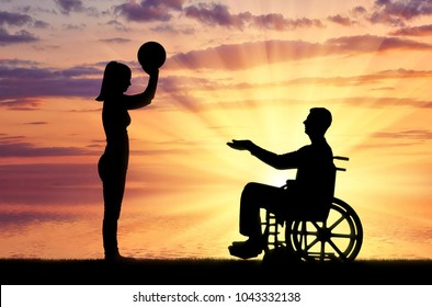 Silhouette of a disabled man in a wheelchair and his wife playing together by the sea. The concept of caring and supporting disabled people in the family