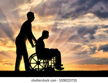 Silhouette of a disabled man in a wheelchair and a nurse in the sunset. The concept of caring for people with disabilities