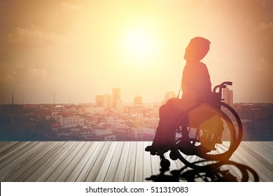 Silhouette of disabled person or wheelchair have sunset background. International Disability Day or Handicapped sport. Paralympics concept.