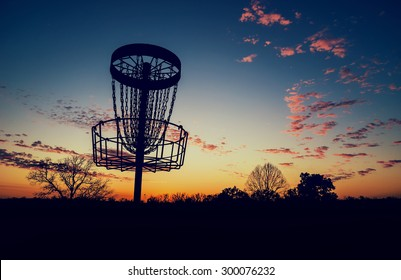 Silhouette of disc golf basket against sunset. Vintage filter effects.