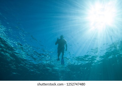 Silhouette of a diver with sunburst from below