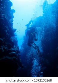 Silhouette of a diver swimming out of the canyon