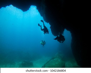 silhouette divers in a cave, koh tao island, thailand