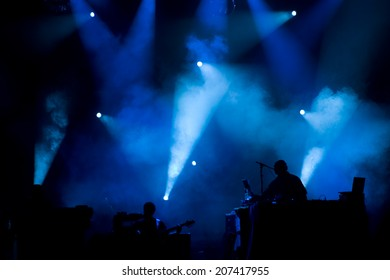 Silhouette of a DJ and bass guitarist playing at music festival with some fabulous blue stage lights in background