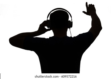 Silhouette of a DJ. He is raising his arms.