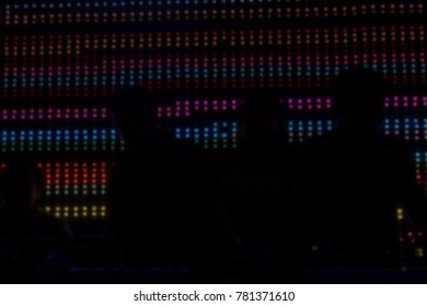 silhouette dj mixing audio music at night club. male sound engineer balancing volume of digital mixer at pub. blur defocused background