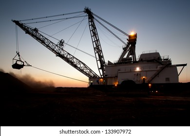 silhouette of drag line working on mine at sunrise with beautiful skies