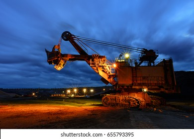 silhouette of drag line working on mine at afer sunset with beautiful skies,One side of huge coal mining drill machine photographed from a ground ,Mining site