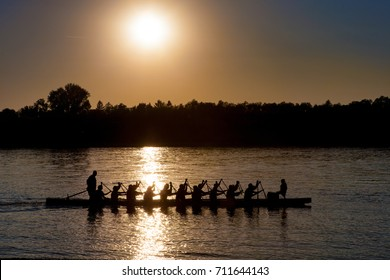 Silhouette of a Dragon boat with paddling people at sunset on Danube river