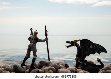 silhouette of dragon and knight on the pebbled shore near the sea