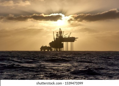 Silhouette of a drilling rig in the North Sea at sunset. Jack up drilling rig.