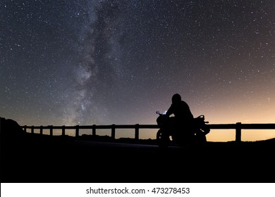 silhouette of driving a motorbike with Milky way landscape on background,