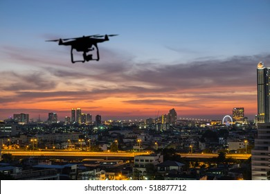 Silhouette of drone flying above the city at sunset time