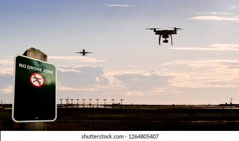 A silhouette of a drone flying near an airport with a no drone sign in the foreground.