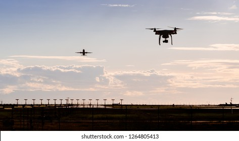 A silhouette of a drone flying near an airport with a aircraft departing in the background.