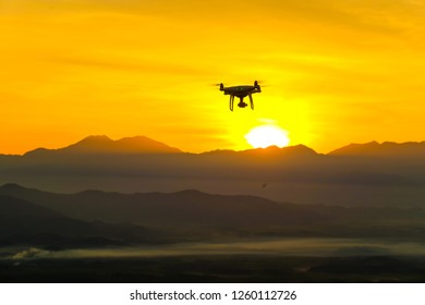 Silhouette Drone flying on mountain sunset sky with cloud, Aerial photography